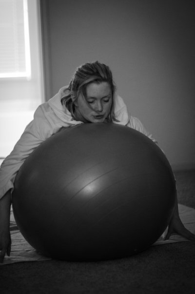Laboring mother lays on birthing ball, breathing through contraction during home birth