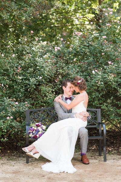 bride sitting on top of groom wearing gray suite with purple bowtie sitting on a bench surrounded by pink roses at Merry Hill Weddings