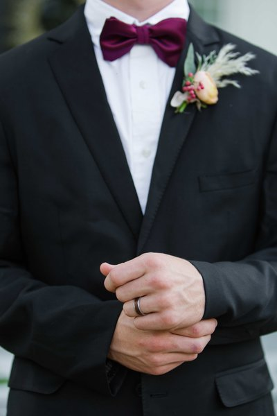 Groom adjusting buttons showing his ring, bowtie and boutonniere