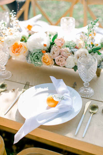wedding reception table decorated with flowers and oranges