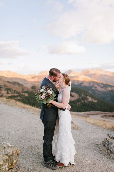 Adventurous wedding couple hiking mountain at loveland pass