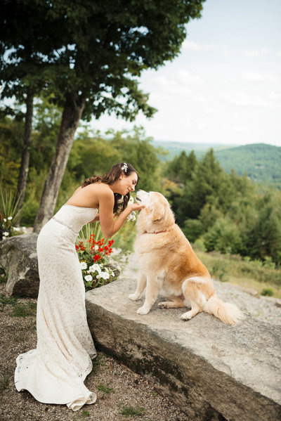 bride kissing dog overlooking mountains at Grante Ridge Estate Norway Maine