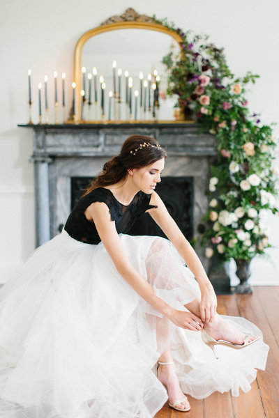 Bride wearing Sweet Caroline gown and Emma Katzka Bridal crown in front of fireplace with floral garland