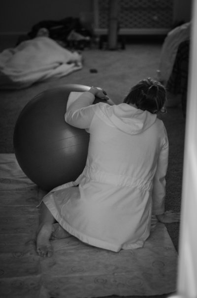 Mother in labor rests her hands on birthing ball during labor