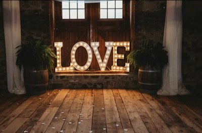 a large love sign in front of the sweetheart table