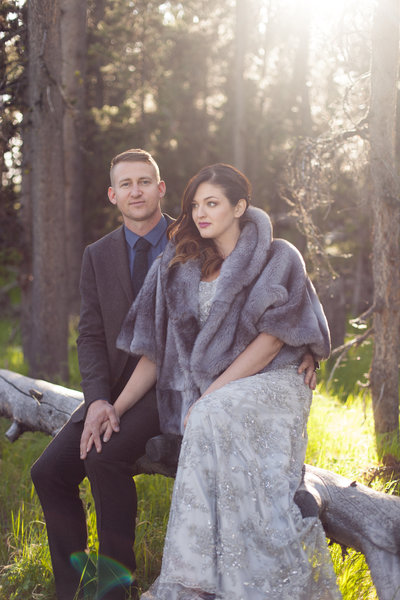 A bride in a coat sits with her groom during an elopement at Yellowstone National Park
