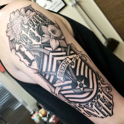 A black and gray tattoo of Betty and florals.
