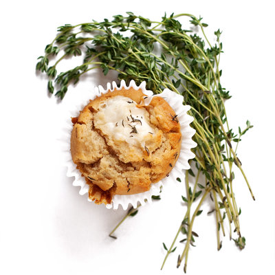 A muffin sits on a white background with thyme around it