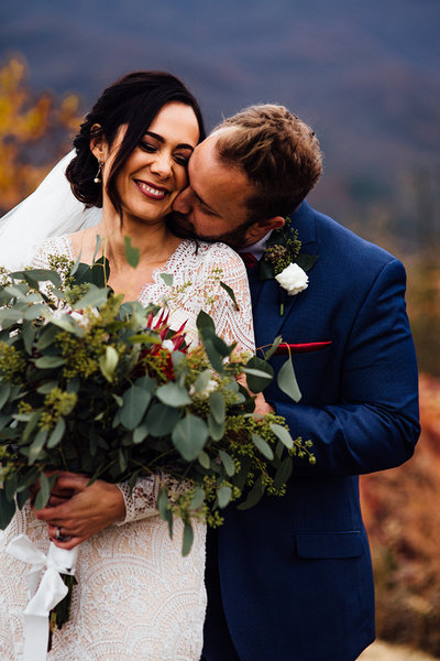 bride and groom giggling together with bouquet during fall wedding