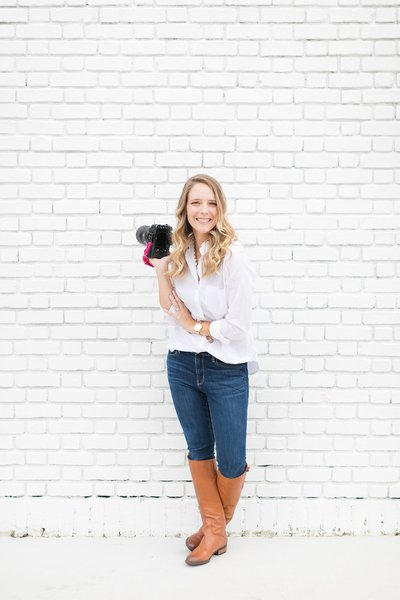 Cassady K Photography holding a camera and standing in front of a white brick wall