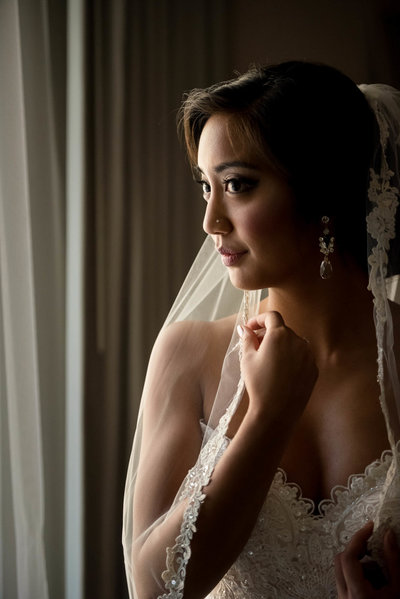 Bridal portrait of bride looking out window adjusting veil Hyatt Regency Boston