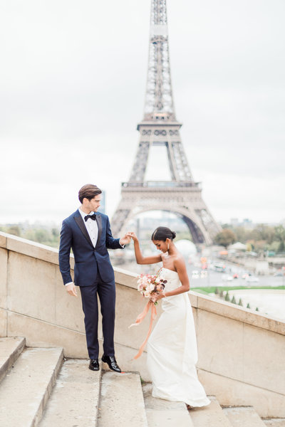 Couple on stairs at eiffel tower in paris france elopement by Costola Photography