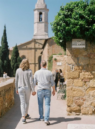 Couple holding hands walking in Pienza during a lifestyle portrait shoot, vacation photography by Rosie Reports