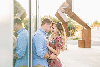 Sacramento CA engagement session couple  leaning on wall cuddling