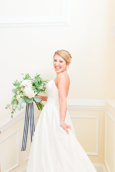Bride posing on staircase with white and greenery bouquet with black and white striped ribbon