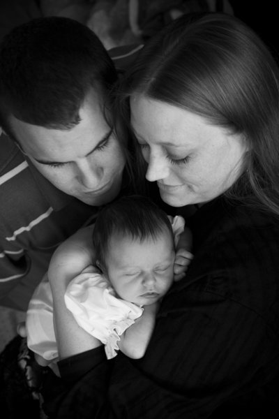 Newborn baby sleeping contentedly with mom and dad a few days after birth
