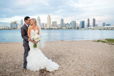 Bride and Groom on beach with San Diego skyline behind them at Centennial Park
