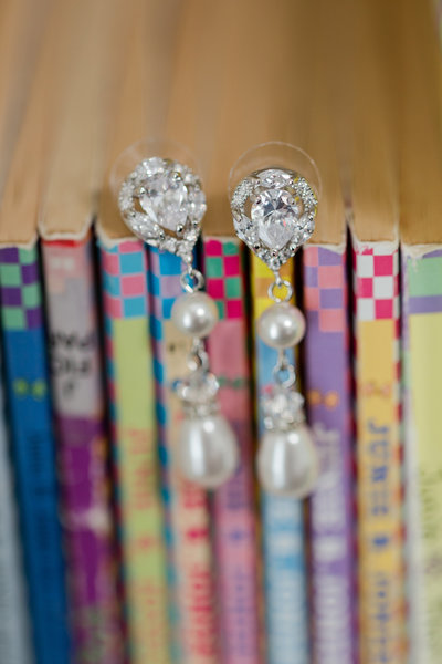 Colorful books lined on a shelf with rhinestone and pearl earrings