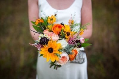 Bride holding bright yellow and orange Summer bridal bouquet at Blooming Hill Farm in New York's Central Valley. New York wedding florist