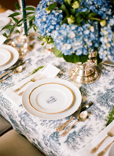 Blue and white wedding table with navy toile Nuage linen and monogram Sasha Nicholas plate and blue hydrangea centerpiece