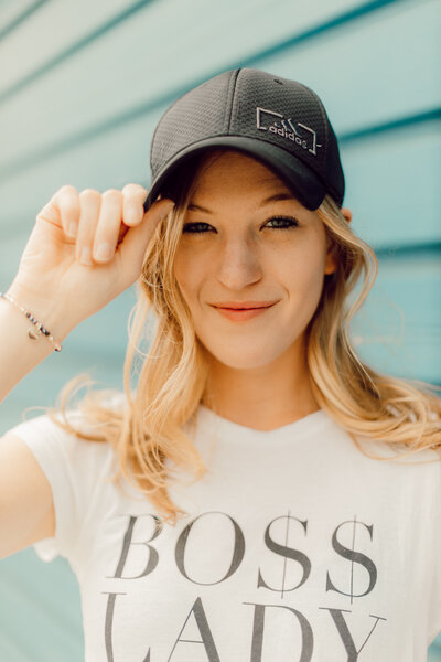 Joelle Elizabeth smiling blue background wearing a Boss Lady tshirt
