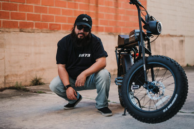 David Castillo of Expose The Heart Photography posing next to his Lithium Cycles Super 73 S1 for Instagram @txpunisher