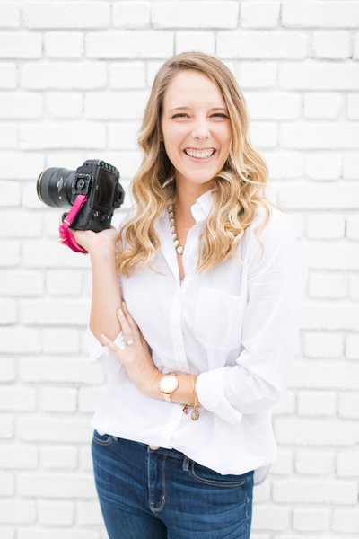 Cassady K Photography smiling at camera in front of white brick wall
