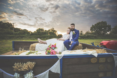 A norfolk bride and groom on hay bales on the back of their tractor at their wedding.