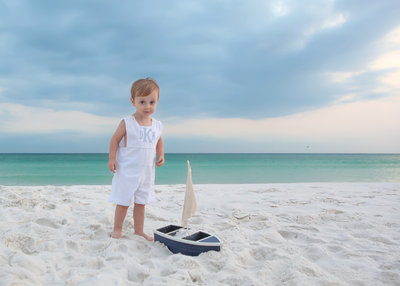 Little boy with a boat plays on the beaches of Destin Florida