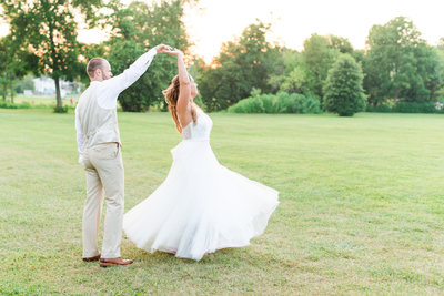 A bride twirls at her Union Mills Barn wedding in Maryland.