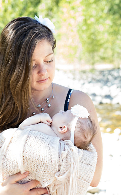 Mother and newborn share tender moment by river