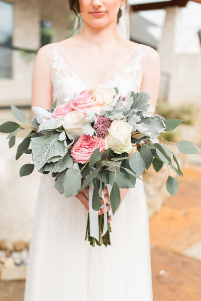 bride holding bouquet of greenery and roses