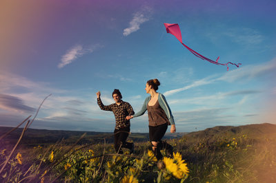 engaged couple fly a kite at rowena crest