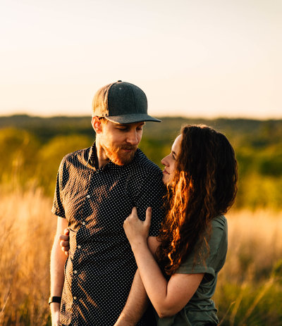 husband wrapping arms around wife at sunset