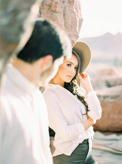 hipster couple in Zion National Park  posing against red rocks for engagement session photographed on medium format film