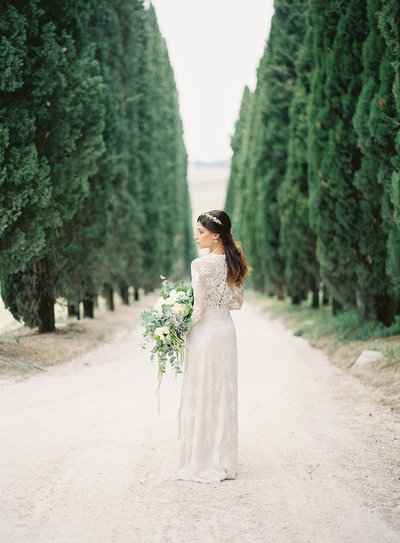 Bride in a pathway surrounded by column of trees in Long Beach