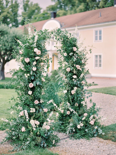 Garden inspired wedding arch with blush roses and greenery at Södertuna Slott