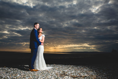 couple on beach against a stormy sky