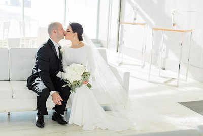bride and groom kissing on white couch