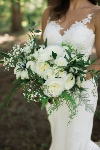 bride in strapless wedding dress holding  white and green bridal bouquet at the Roundhouse in Beacon, New York in the Hudson Valley. Hudson Valley wedding florist