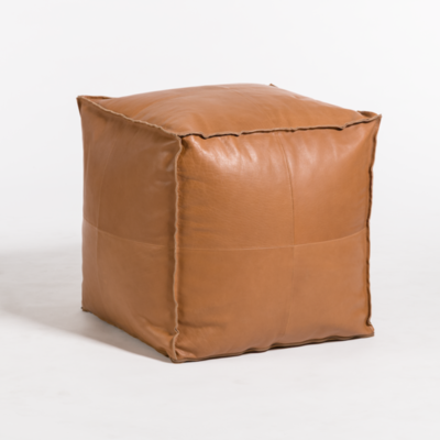 A tan, cube-shaped, leather ottoman from Hockman Interiors