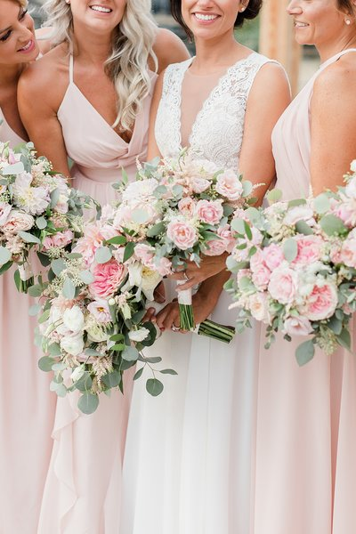 Bridesmaids laughing and smiling with pink bouquets