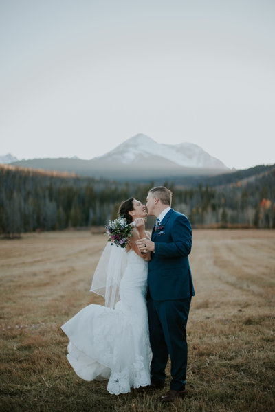 outdoor fall vail colorado weddings, vail wedding photographer, bride wearing vintage fur, gray suit, green bouquet, bride and groom kissing in aspens, colorado adventure photographer, destination wedding photographers, mountain wedding photographers, mountain elopement photography, salty spruce studio