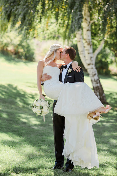 Bride and Groom kissing with bouquet Siren Song Winery Lake Chelan