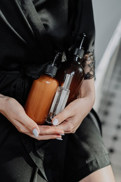 person-holding-orange-and-black-bottle-4154192