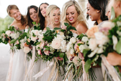 Bridesmaids in blush and grey chiffon dresses with Munster Rose bouquets