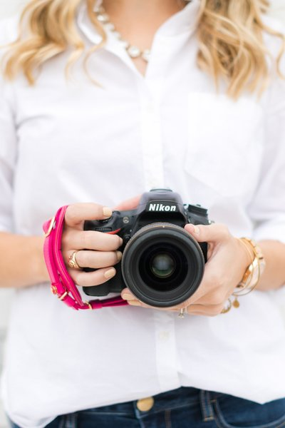 Cassady holding Nikon D750 with a hot pink strap