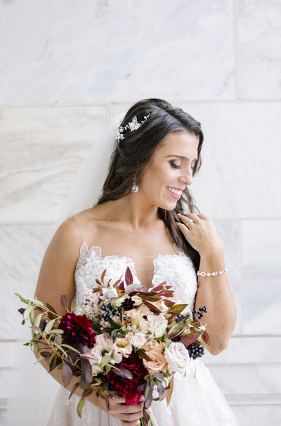 bride in front of stone wall holding red bouquet