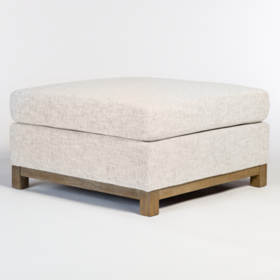 Cream colored ottoman with square top at Hockman Interiors