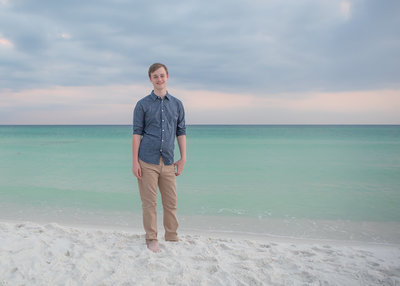 high school senior portrait boy on the beach during a family session